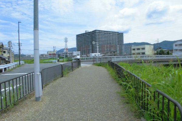 六地蔵店橋が見えたら橋を渡り、川沿いの歩道を左へ曲がります。